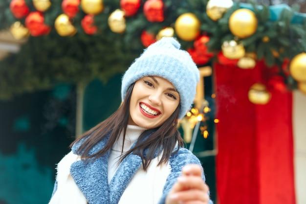 Emotionele jonge vrouw draagt blauwe jas en geniet van vakantie met bengaalse lichten