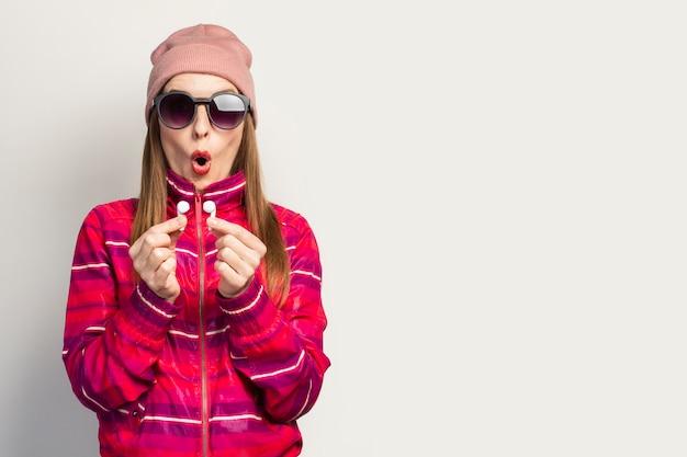 Emotionele jonge vrouw in glazen, een hoed en een roze sportjack met een verbaasd gezicht houdt draadloze koptelefoon.