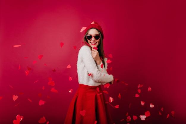 Emotionele jonge vrouw in rode hoed en zonnebril staande op bordeaux ruimte op feestje