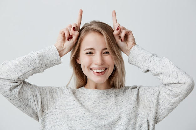 Emotionele jonge vrouw in trui breed glimlachend, spottend, gezichten trekken, wijsvingers boven haar hoofd