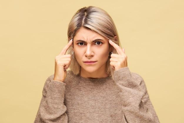 Emotionele jonge vrouw in trui die aan hoofdpijn lijdt, met hersenbelasting tempels masseren met vingers, gefrustreerd voelen door verontwaardiging, fronsen, proberen na te denken