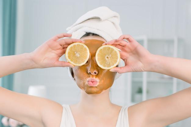 Emotionele jonge vrouw in witte handdoek op het hoofd en met gezichtsmasker en helften van rijpe citroen op witte ruimte. foto van vrouw die kuuroordbehandelingen ontvangt. schoonheid en huidverzorging concept