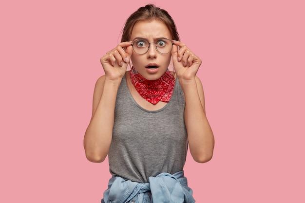 Emotionele jonge vrouw met bril poseren tegen de roze muur