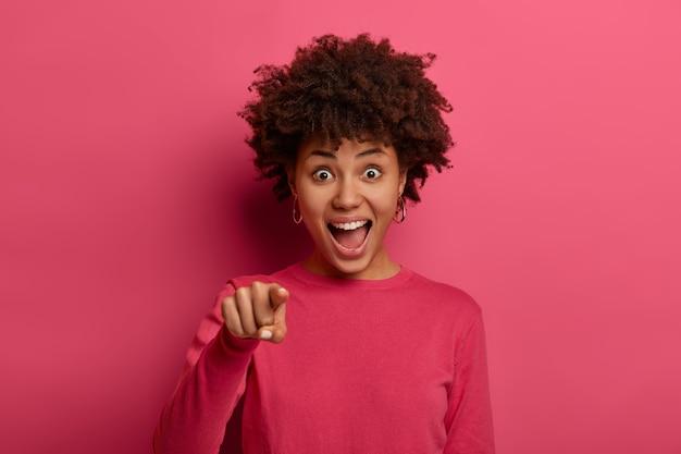 Emotionele jonge vrouw met een donkere huid ziet er opgewonden en opgewekt uit, wijst direct met de wijsvinger, kiest iets of kiest iemand, draagt een roze trui, poseert binnen. mensen en keuze.