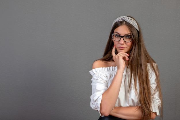 Emotionele jonge vrouw met eyeglases op donkere achtergrond met exemplaarruimte