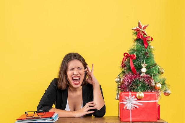 Emotionele jonge vrouw sluit haar ogen zittend aan een tafel in de buurt van versierde kerstboom op kantoor op geel