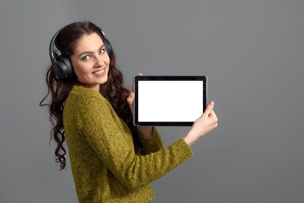 Emotionele jonge vrouw weergegeven: tabletcomputer met leeg touchscreen met kopie ruimte, geïsoleerd op grijs oppervlak