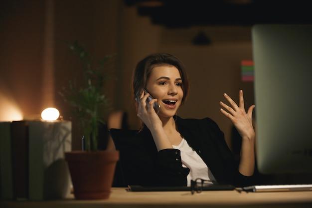 Emotionele jonge vrouwenontwerper die telefonisch spreekt.