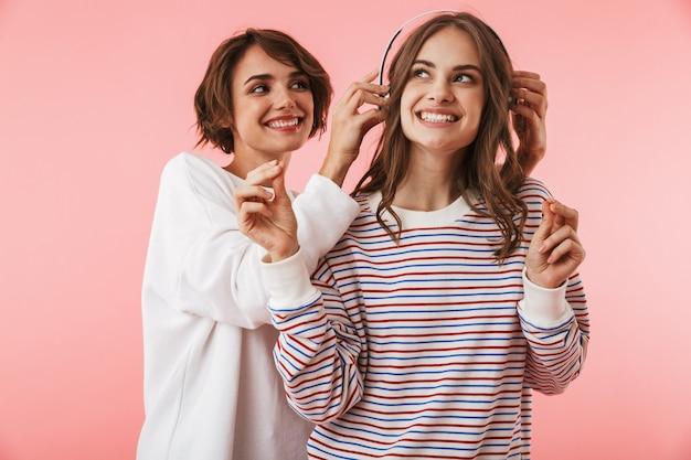 Emotionele jonge vrouwenvrienden die geïsoleerde luistermuziek met hoofdtelefoons stellen.