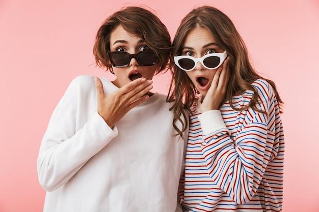 Emotionele jonge vrouwenvrienden die over roze muurachtergrond worden geïsoleerd die zonnebril draagt.