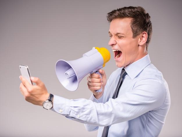 Emotionele jonge zakenman die op de telefoon spreekt.