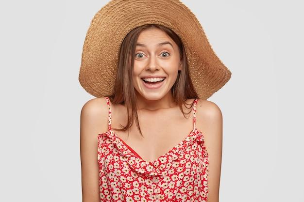 Emotionele jongedame heeft vrolijke uitdrukking, draagt zomer strooien hoed en modieuze jurk