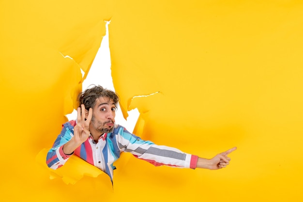 Emotionele jongeman die iets aan de linkerkant wijst en drie laat zien in een gescheurde gele papieren gatenachtergrond