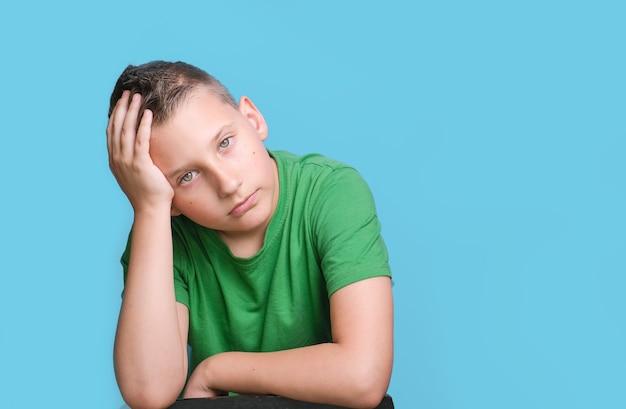 Emotionele jongen die het hoofd bedekt met de hand die moe is hoofdpijn die emotie toont