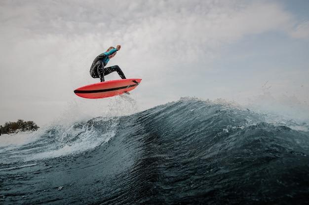 Emotionele jongen gekleed in zwarte en blauwe zwembroek surfen springen op oranje bord