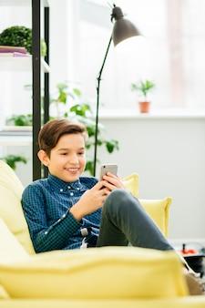 Emotionele jongen ontspannen op gele sofa met kussens en glimlachen terwijl hij naar het scherm van zijn smartphone kijkt