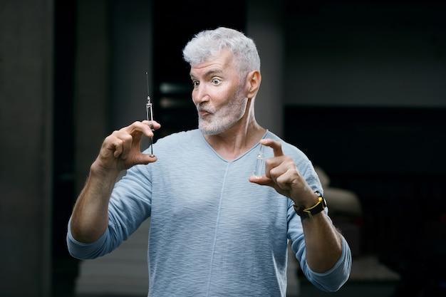 Emotionele knappe grijsharige senior man gevaccineerd met een spuit in de hand. vaccinatie en zorgconcept