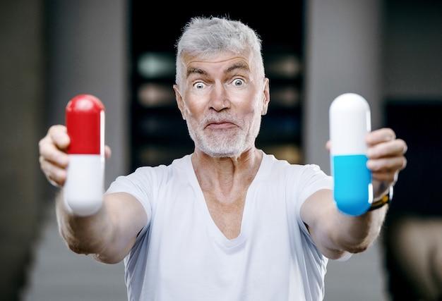 Emotionele knappe grijsharige senior man met een grote rode en blauwe pil in zijn hand. geneeskunde en gezondheidszorg concept