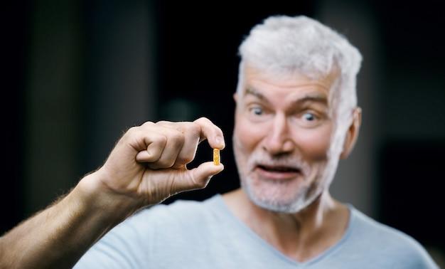 Emotionele knappe grijsharige senior man met een pil in zijn hand. geneeskunde en gezondheidszorg concept