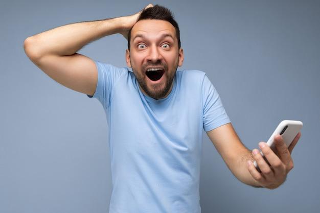 Emotionele knappe jonge bebaarde donkerbruine man met dagelijkse blauwe t-shirt geïsoleerd