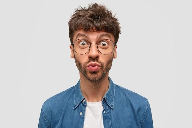 Emotionele knappe jonge kerel pruilt lippen van verwondering, staart door een grote bril, heeft donkere stoppels, gekleed in een spijkerblouse, poseert tegen een witte muur