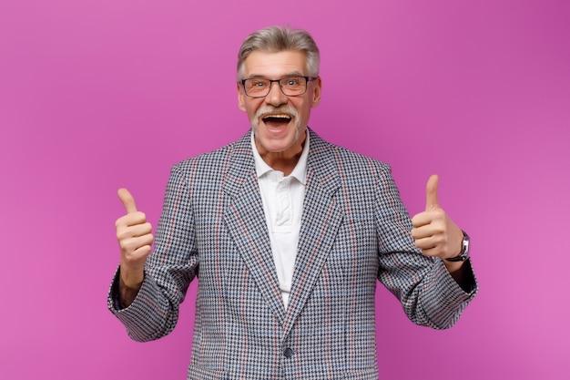 Emotionele knappe volwassen man met een jas die naar de voorkant kijkt met een goed enkel gebaar tegen een violette muur