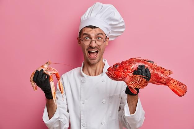Emotionele kok poseert met zeevruchten in wit uniform, schreeuwt luid, nodigt uit om zijn restaurant te bezoeken