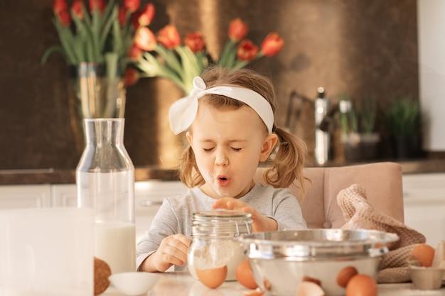 Emotionele lachen expressie kind meisje met bloem op neus en gezicht koken verjaardagstaart in witte zonnige keuken met lentebloemen. thuis bakkerij..