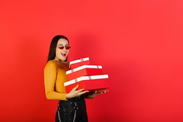 Emotionele lachende mooi meisje met stapel geschenkdozen geïsoleerd op rood oppervlak met kopie ruimte.