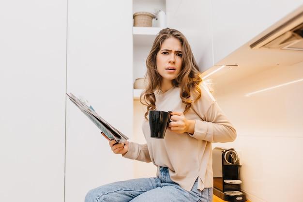 Emotionele langharige vrouw draagt een beige overhemd koffie drinken in haar keuken