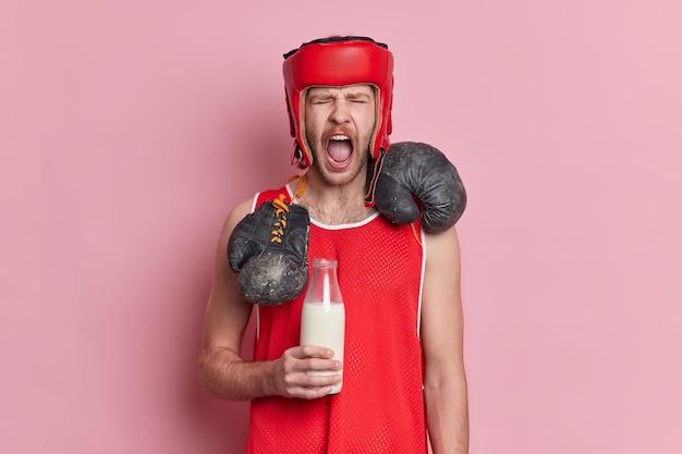 Emotionele man bokser in sport outfit houdt fles melk houdt aan eiwitdieet krijgt vitamines voor spieren roept luid.