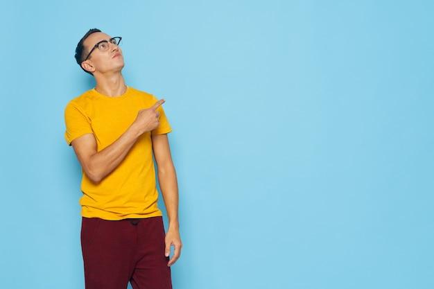 Emotionele man die hij met zijn hand gele t-shirt bril blauw gebaart