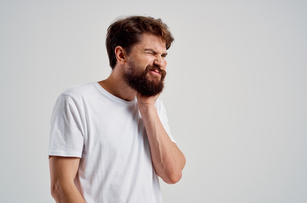 Emotionele man die vasthoudt aan de pijn in tanden lichte achtergrond. hoge kwaliteit foto