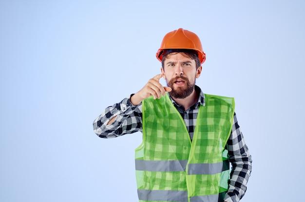Emotionele man groen vest oranje helm workflow handgebaren geïsoleerde achtergrond