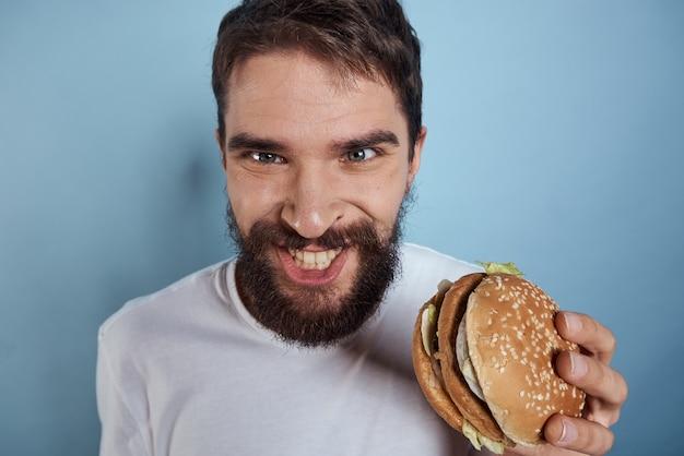 Emotionele man hamburger fastfood dieet voedsel close-up blauwe achtergrond. hoge kwaliteit foto