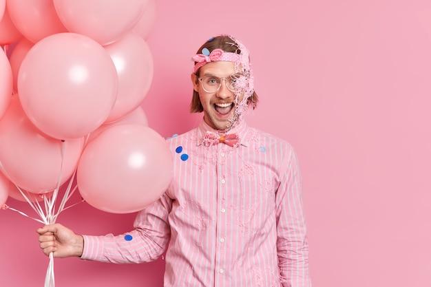 Emotionele man heeft crème op gezicht viert iets brengt vrije tijd door op feestje houdt bosje opgeblazen ballonnen uitroept vrolijk draagt grote bril formeel shirt met vlinderdas omgeven door confetti