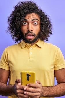Emotionele man hold gebruik smartphone gelezen kreeg melding afkeer schreeuw omg, hij is verrast door nieuws of bericht, geïsoleerd