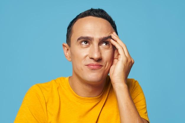 Emotionele man houdt zijn hand in de buurt van zijn gezicht woede grimas geel t-shirt blauw opzoeken