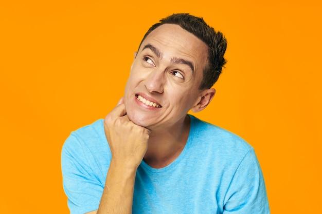 Emotionele man in blauwe t-shirt die gele achtergrond opzoekt