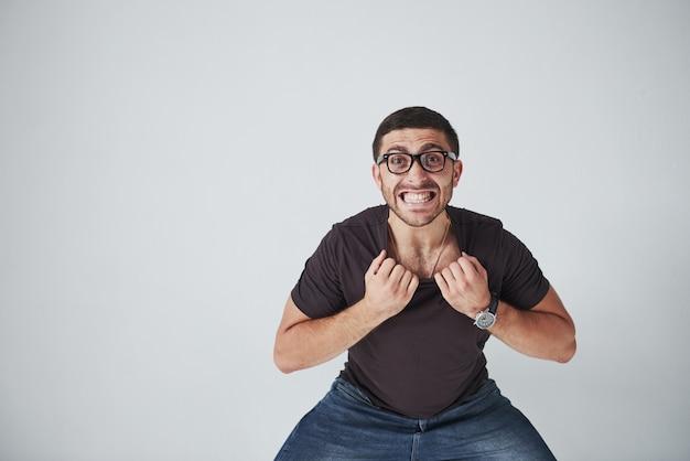 Emotionele man in casual kleding en met een bril houdt zichzelf vast aan de kraag van een t-shirt