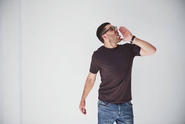 Emotionele man in casual kleding schreeuwt luid alsof iemand belt.