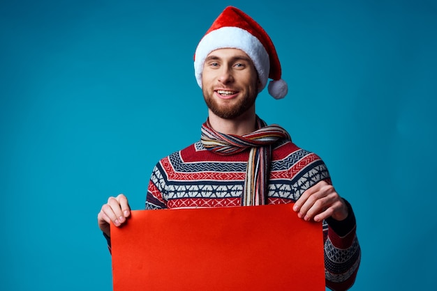 Emotionele man in een kerstmuts met een banner vakantie blauwe achtergrond. hoge kwaliteit foto