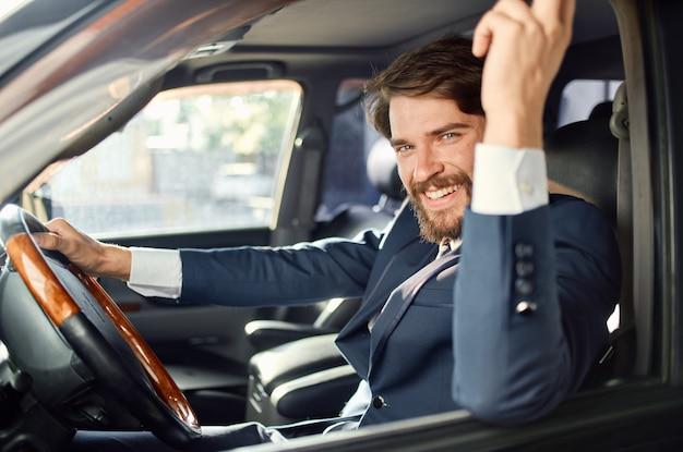 Emotionele man in een pak in een auto een reis naar het werk communicatie via de telefoon