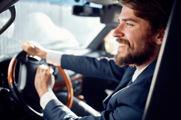 Emotionele man in een pak in een auto een reis naar het werk rijk