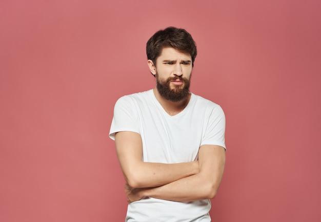 Emotionele man in een wit t-shirt serieuze blik roze achtergrond