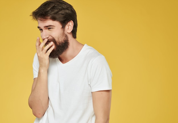 Emotionele man in een witte t-shirt handgebaren woede gele achtergrond