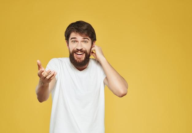 Emotionele man in een witte t-shirt handgebaren woede studio