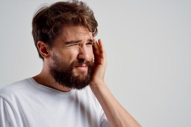 Emotionele man in een witte t-shirt hoofdpijn migraine problemen geïsoleerde achtergrond