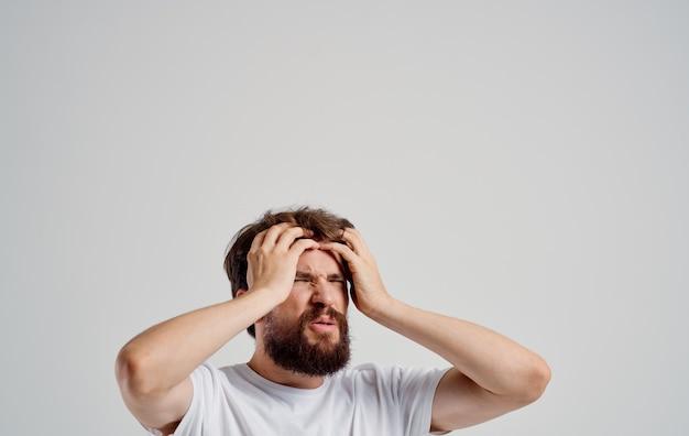 Emotionele man in een witte t-shirt hoofdpijn migraine problemen studio behandeling