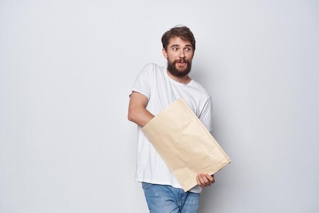 Emotionele man in een witte t-shirt met een papieren zak in zijn handen mocap close-up